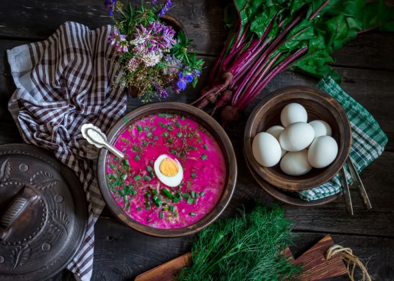 Russian cold soup with beetroot, bowl,spoons, eggs,greenery on dark wooden table. Style rustic. Selective focus.